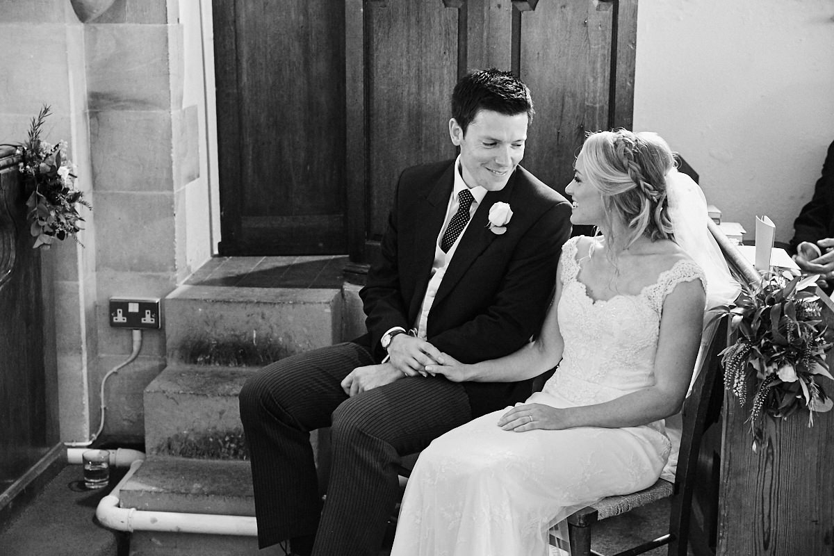 the bride and groom smiling at each other while sitting listening to the wedding sermon