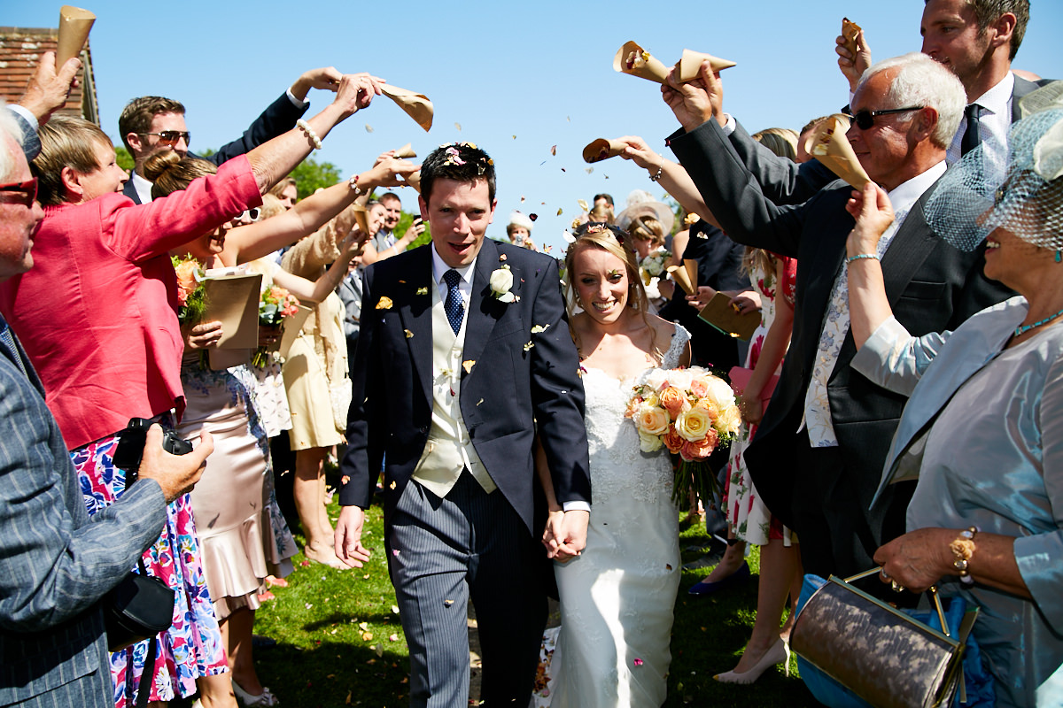 the bride and groom walking between guests as they throw confetti