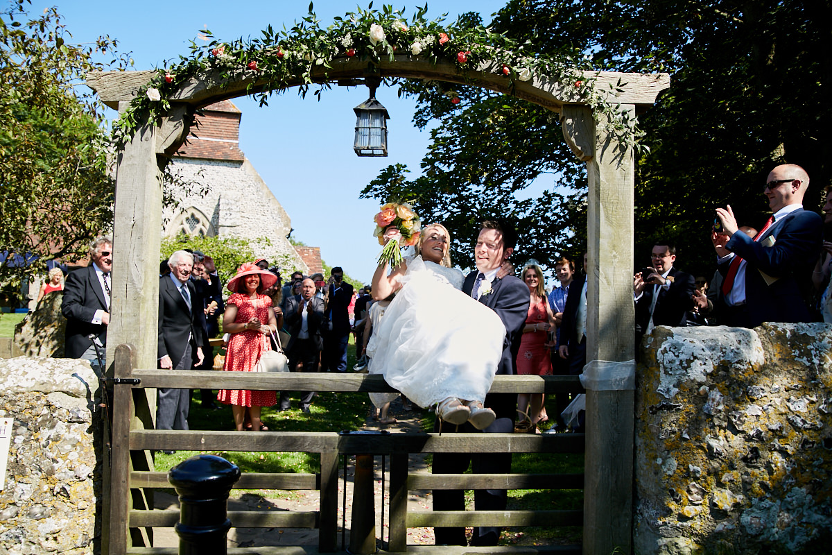 the groom lifting the bride over the gate