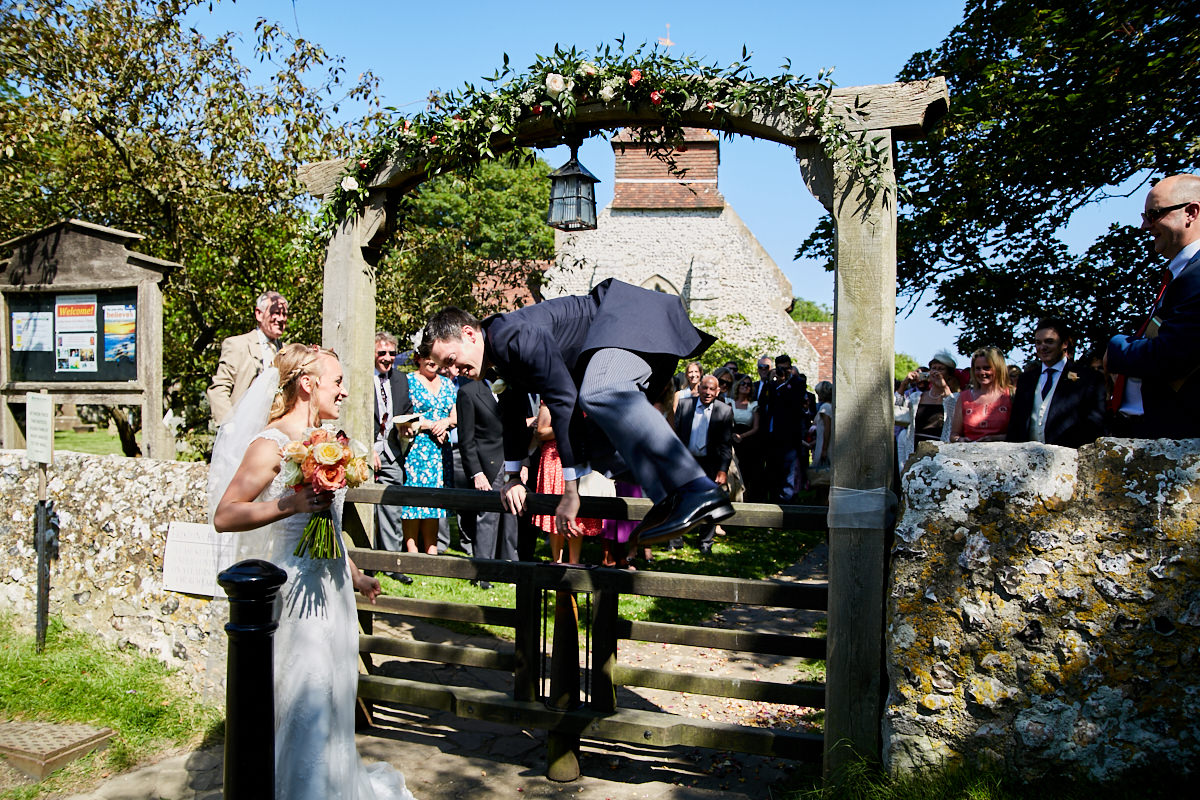 the groom jumping over the gate