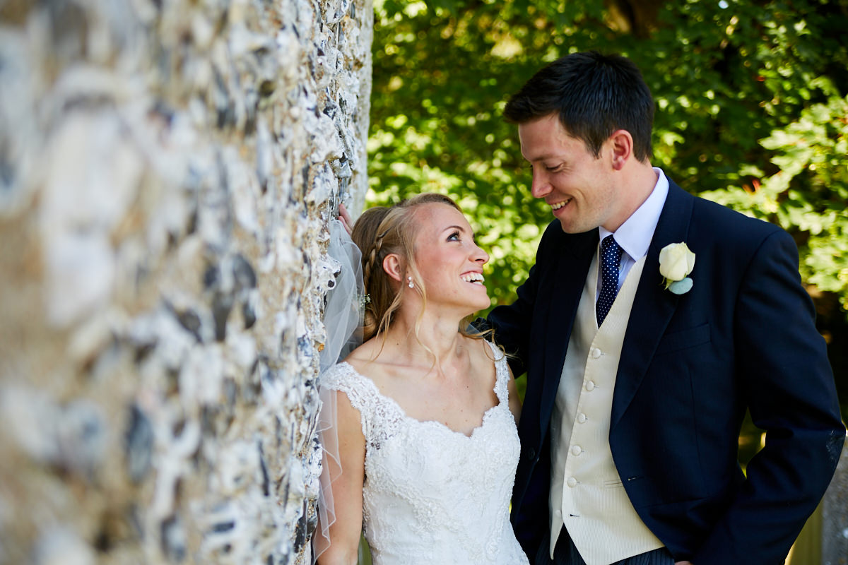 the bride and groom looking at each other while they rest against a flint wall in Sussex