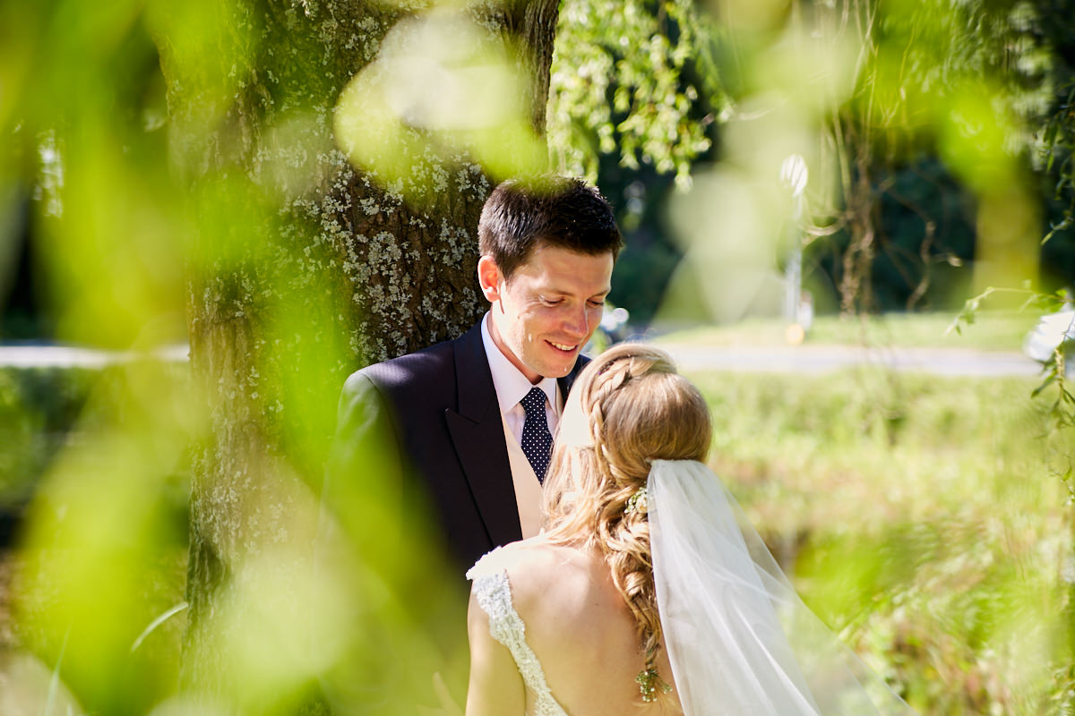 the bride and groom under a willow tree by a pond at their Sussex marquee wedding