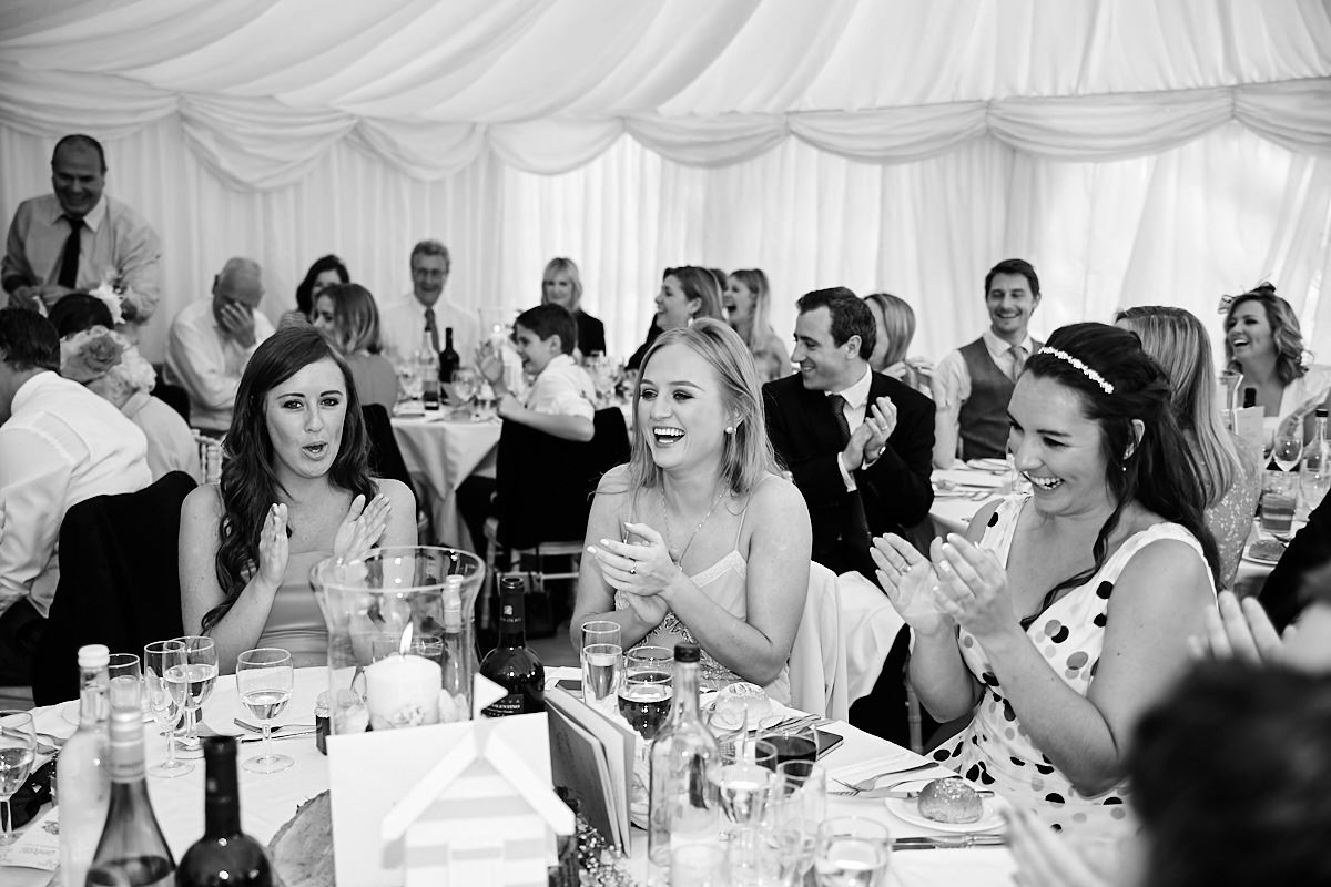 guests clapping as the bride and groom enter the marquee at their wedding