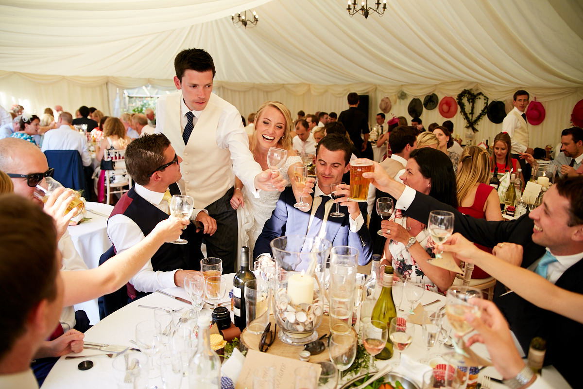 the bride and groom raise a glass with guests