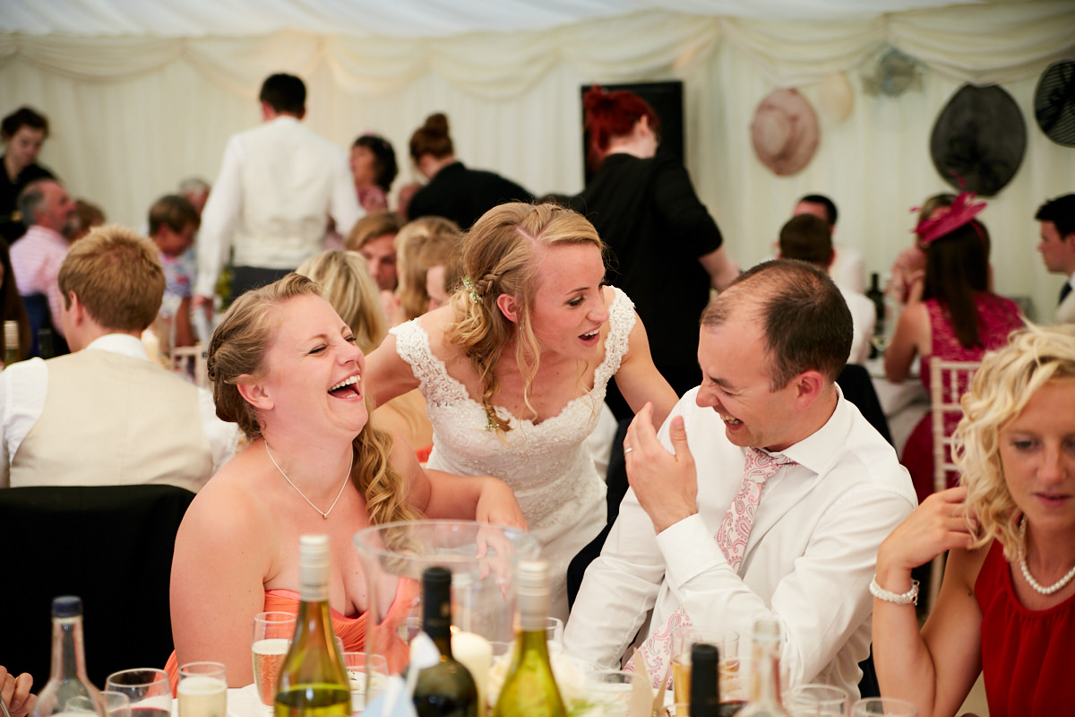 guests laugh at a joke the bride tells