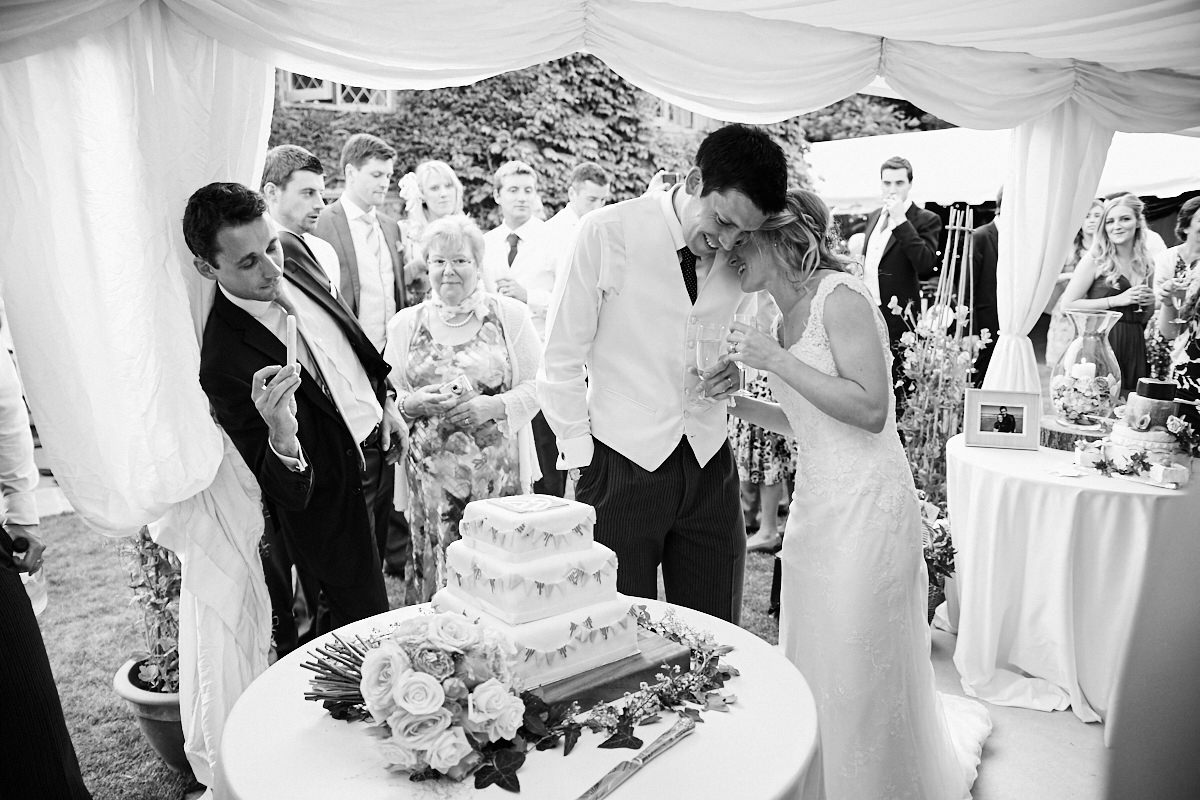 the bride and groom go to cut the cake while a guest takes a photo of it