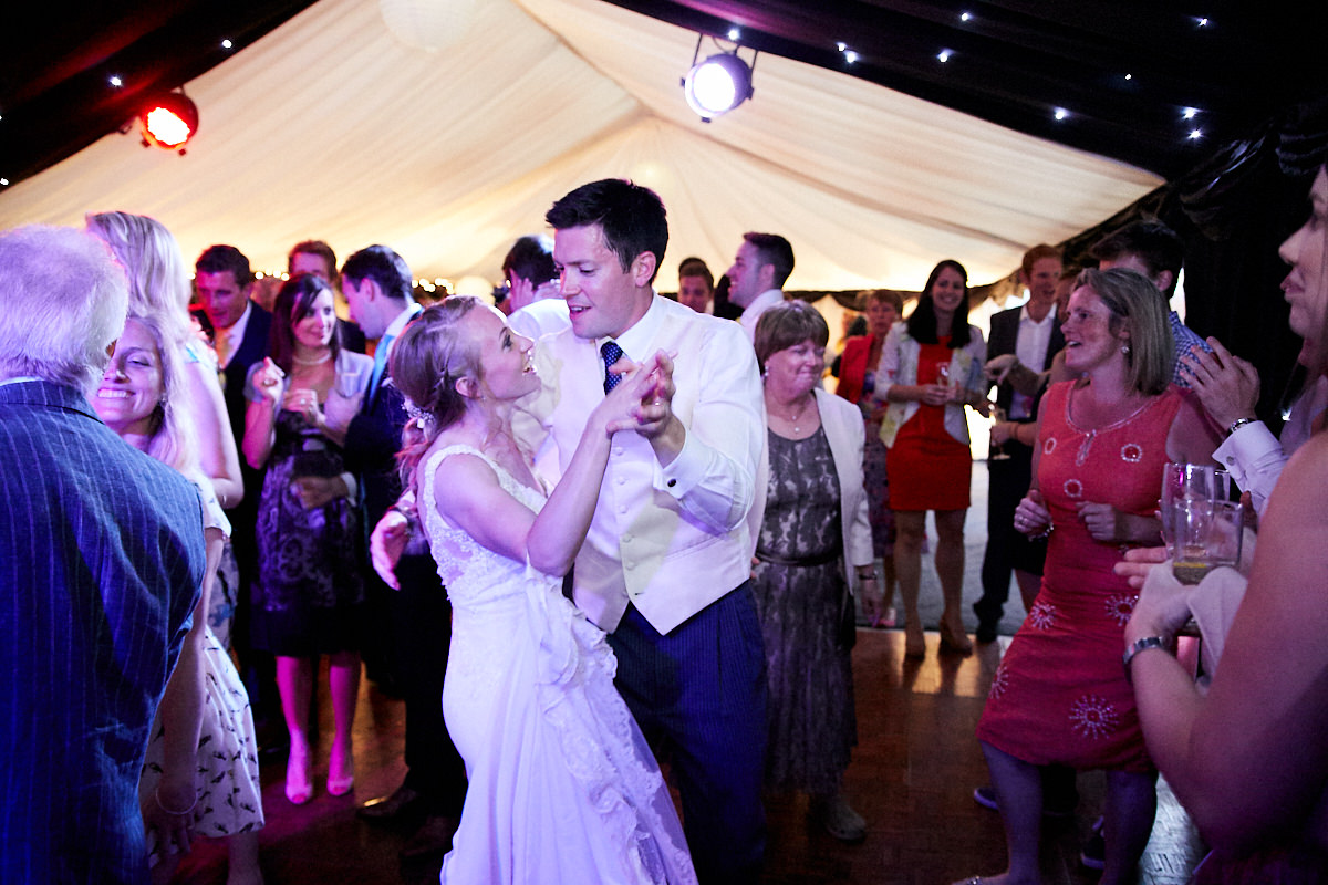 the bride and groom dancing together amongst their guests at their wedding