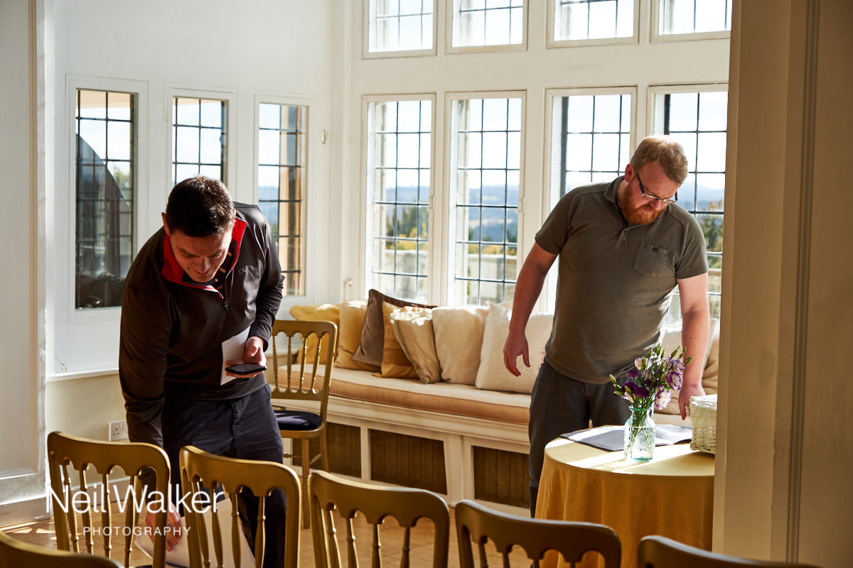 the groom and the celebrant putting the finishing touches to the ceremony room