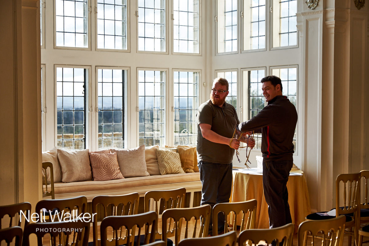 the groom and the celebrant getting the ceremony room ready
