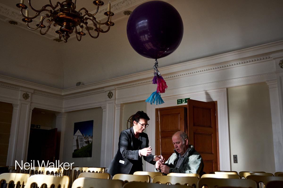 guests tying balloons to chairs in the Drawing Room at Greyfriars House ready for the wedding ceremony