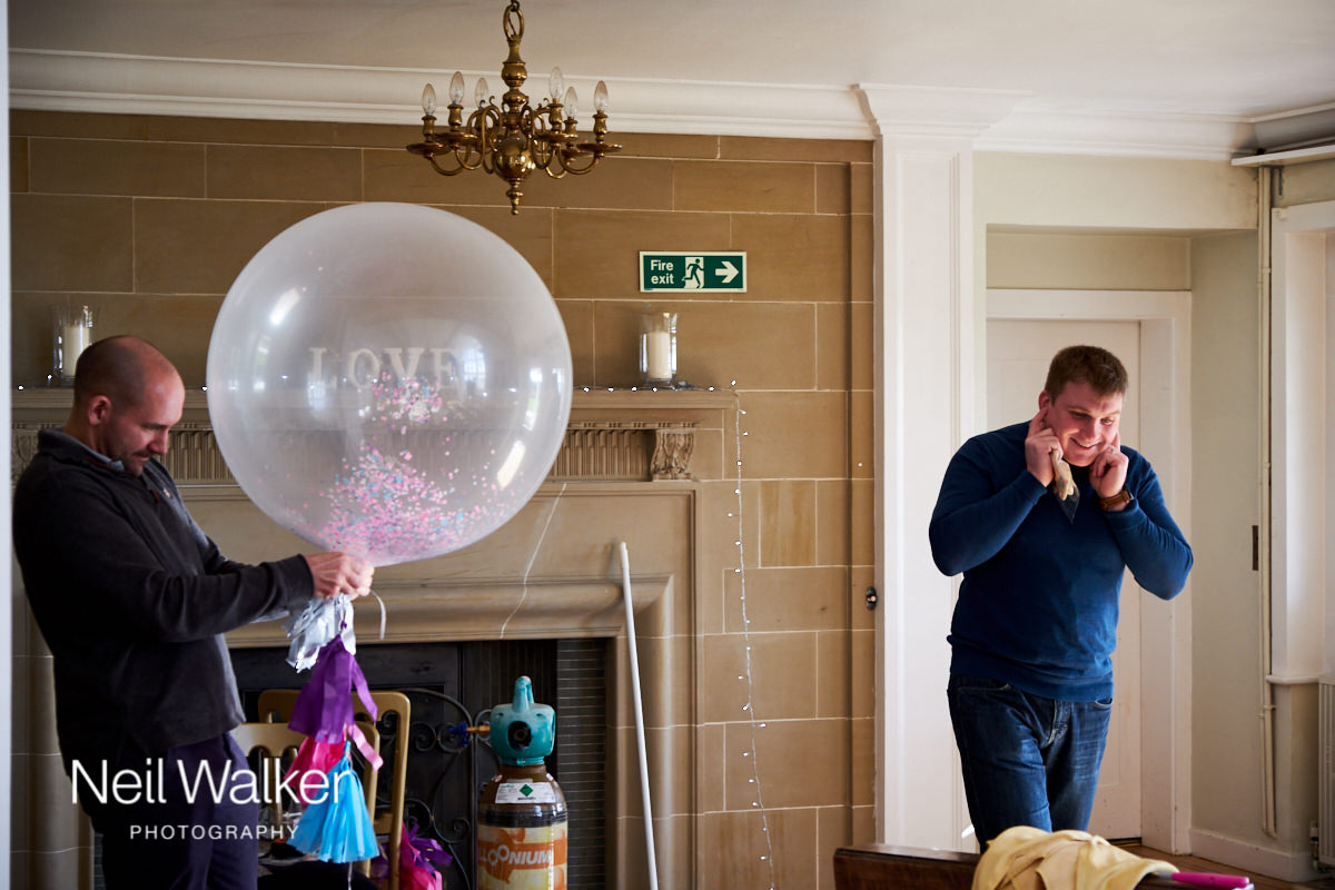 the best man with his fingers in his ears while blowing up balloons with one of the ushers