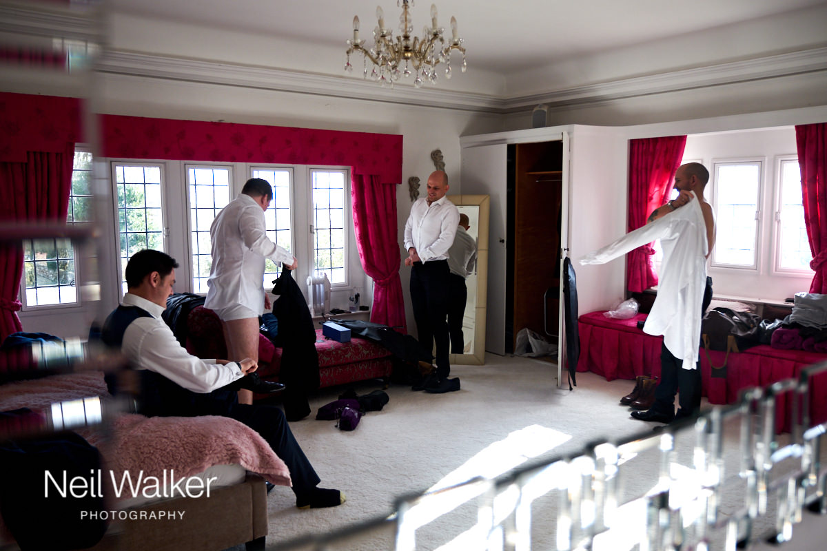 the groomsmen getting changed into their wedding suits