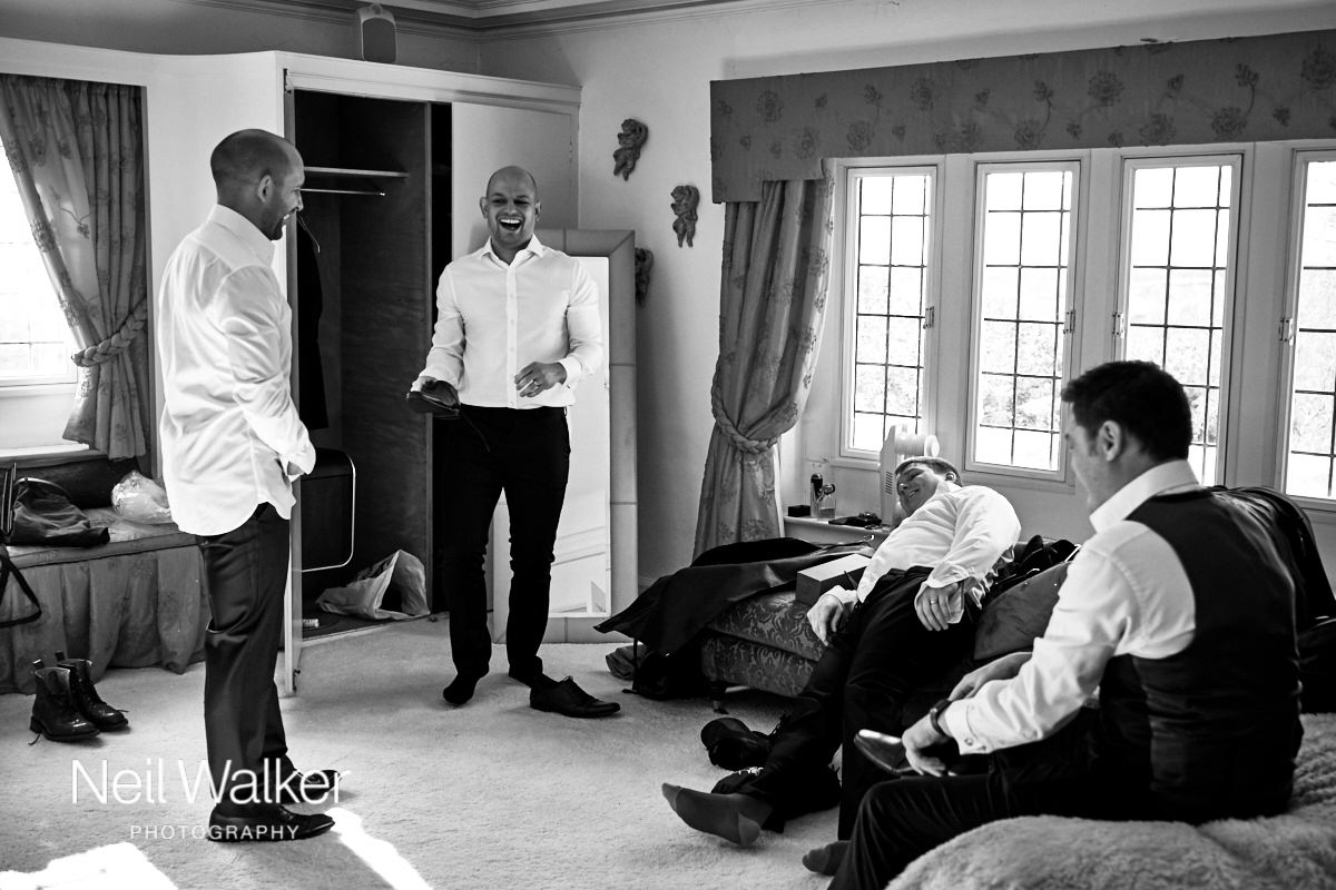 a groomsman laughing while he gets changed for the wedding