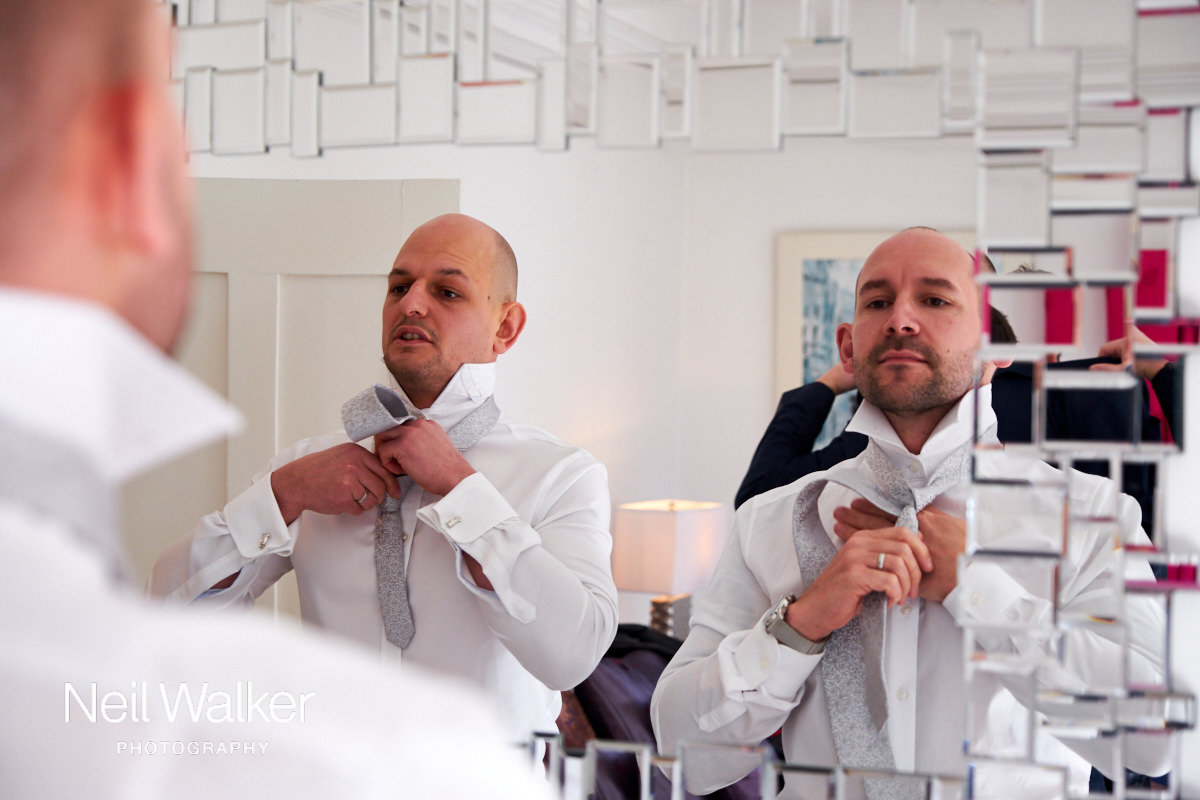 two ushers tying their ties in the mirror