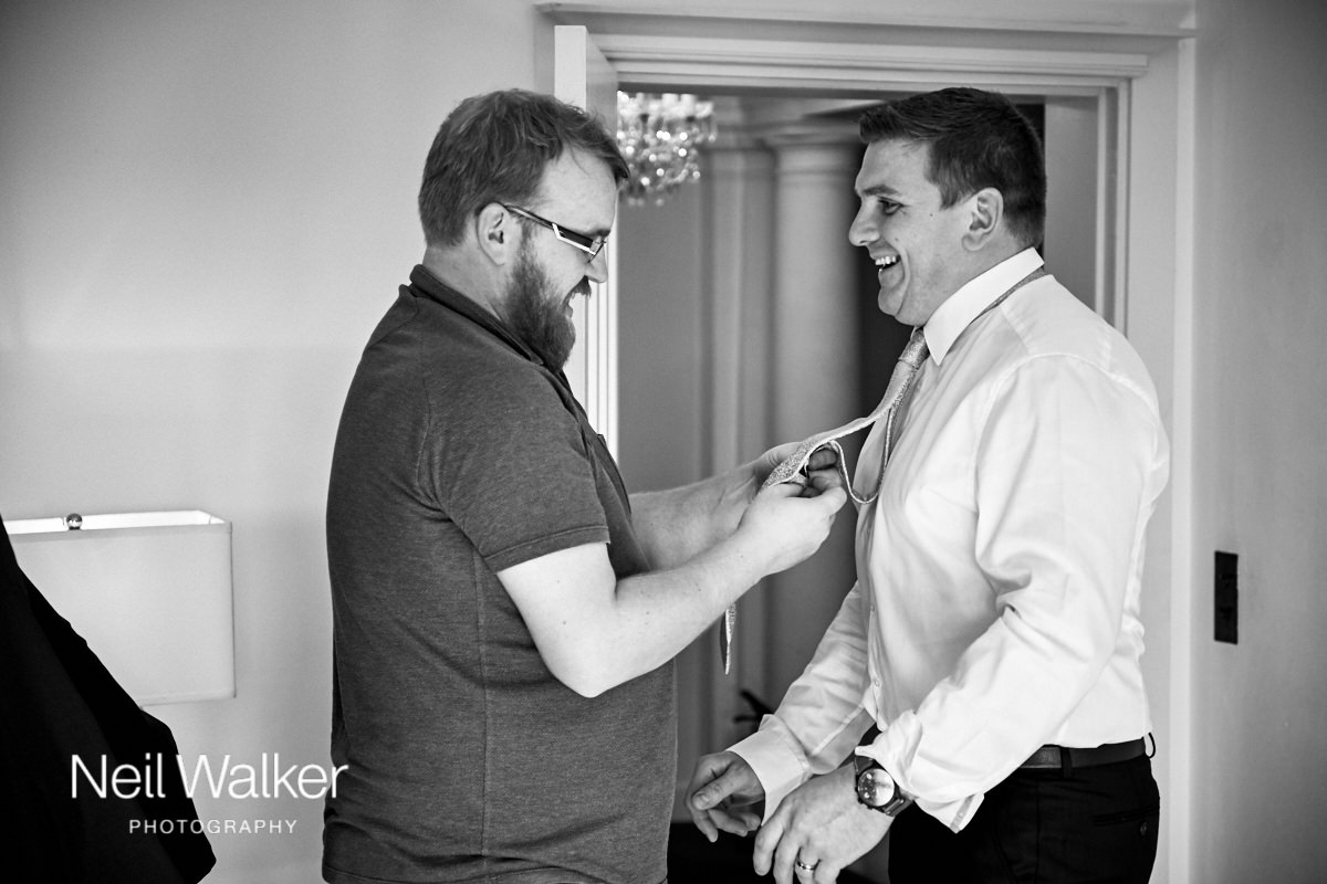 the celebrant ties a groomsman's tie for him