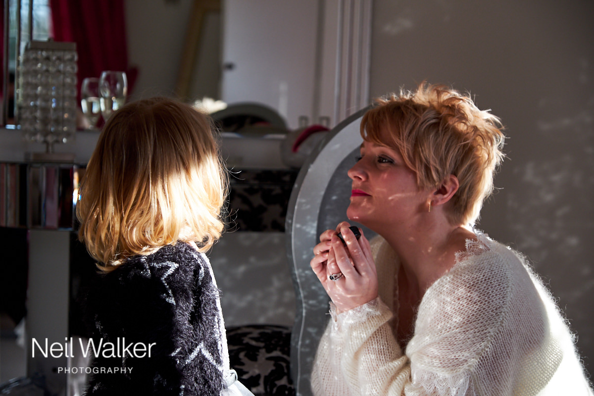 the bride and her daughter putting the finishing touches to their makeup before going down to the wedding ceremony