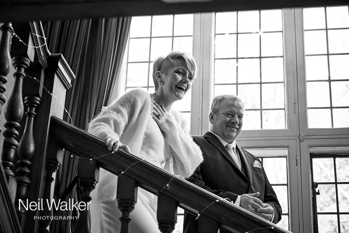 the bride laughing as she comes downstairs with her father for the wedding ceremony at Greyfriars House