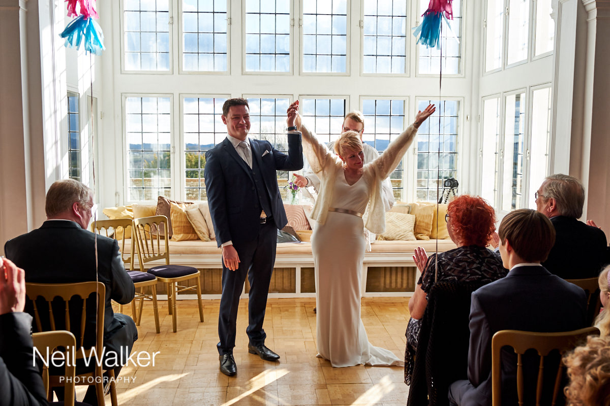 the guests cheer at the end of the wedding ceremony