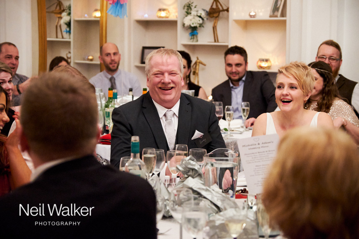 the bride's father laughing at the groom's speech