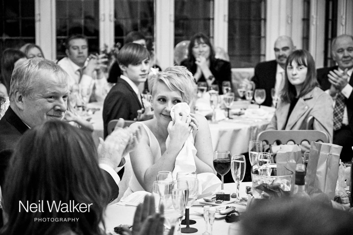 the bride wiping away a tear during her husband's speech