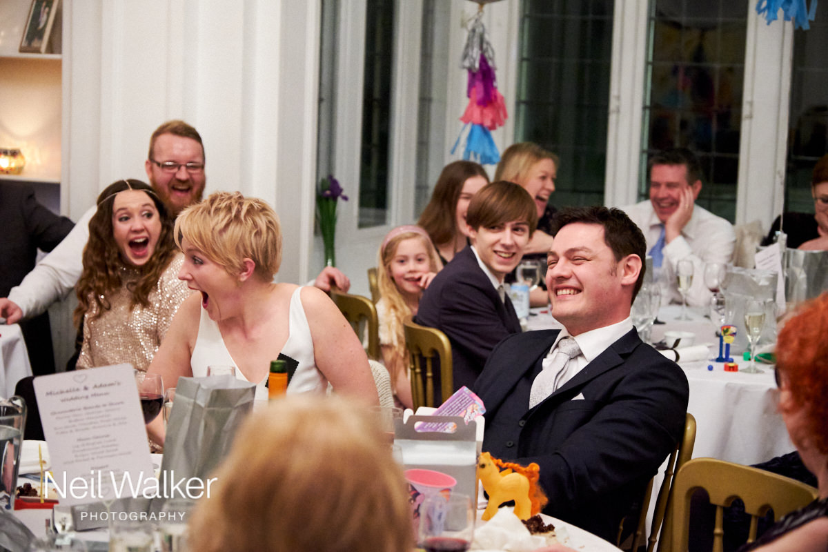 the groom laughing during the father of the groom's speech