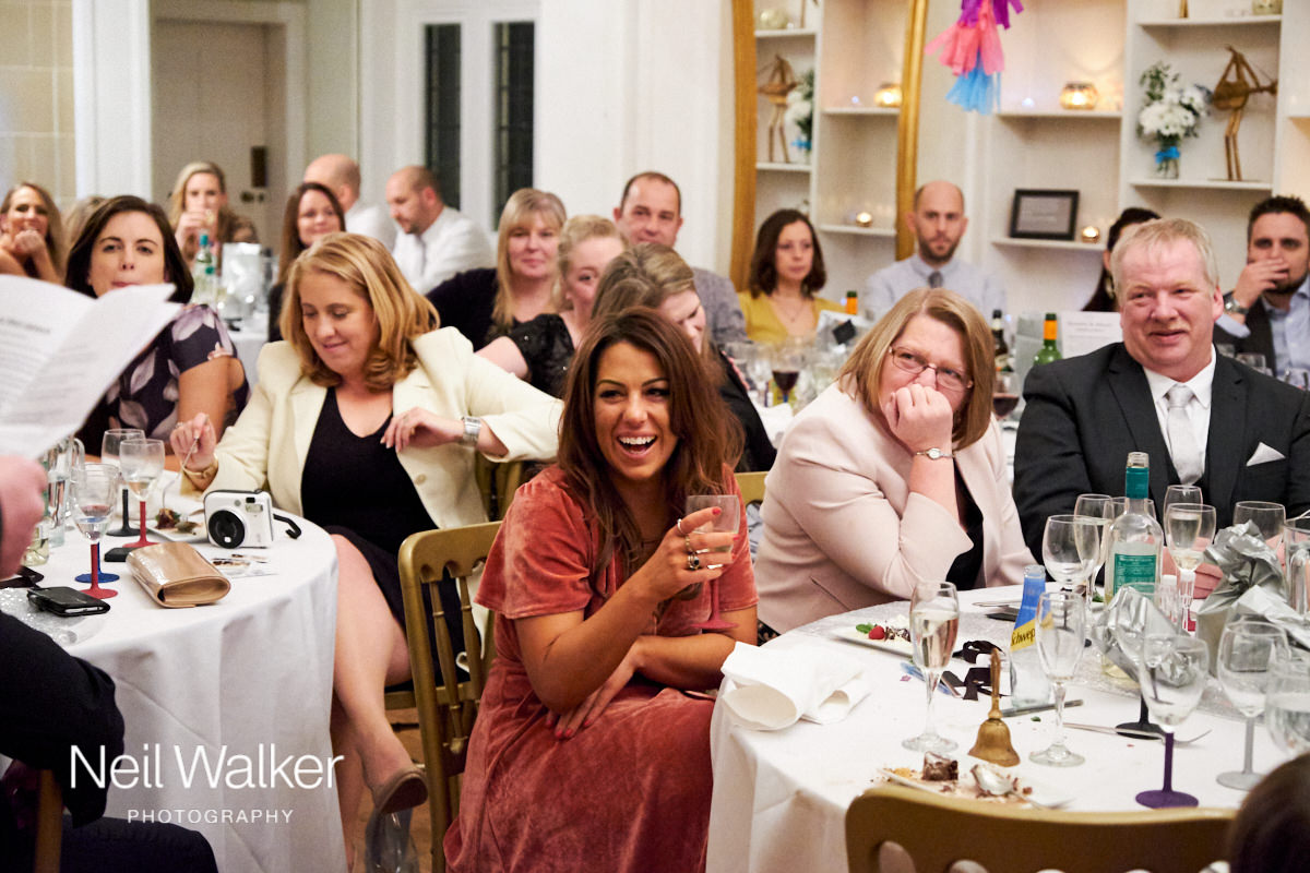 guests laughing during the best man's speech