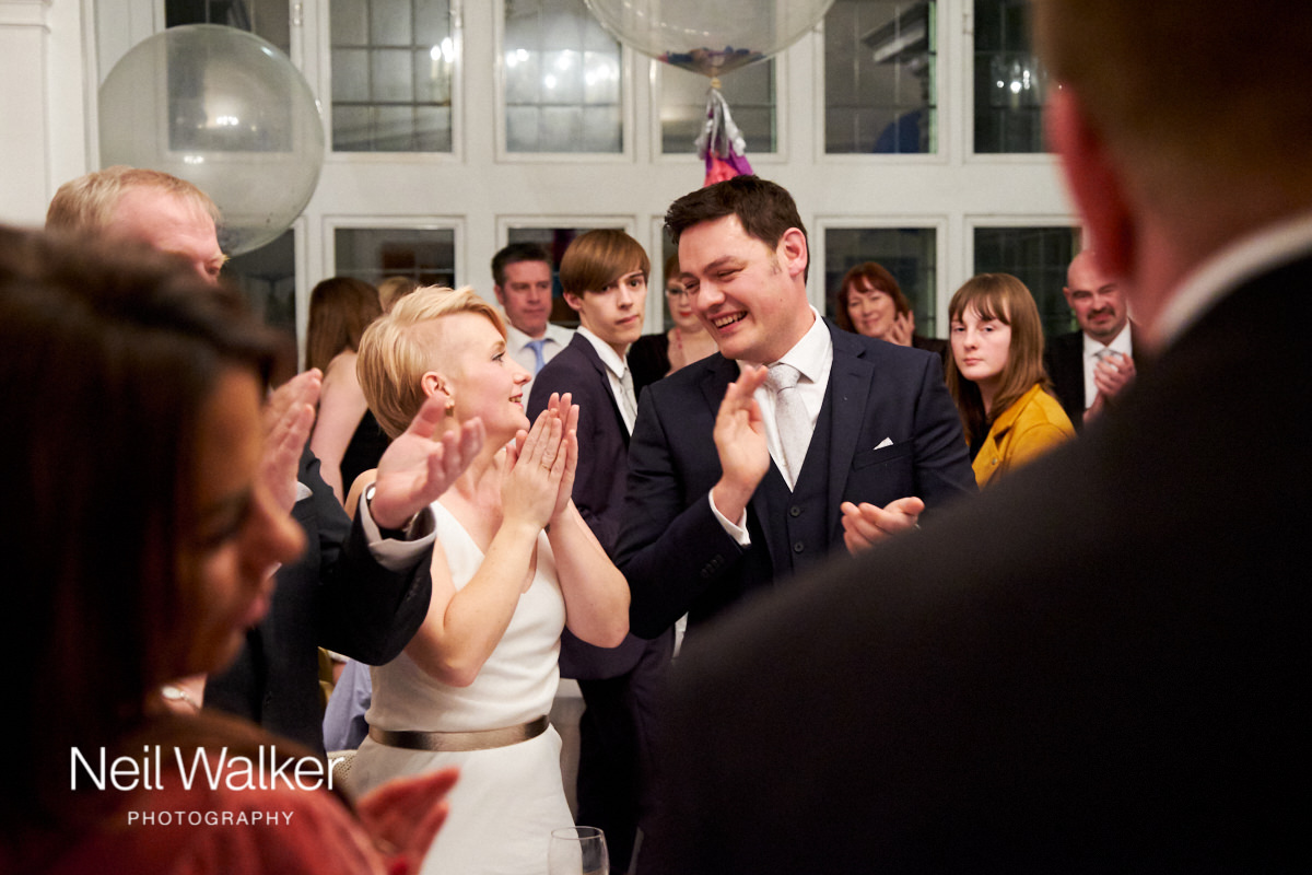 the bride and groom clapping the best man's speech