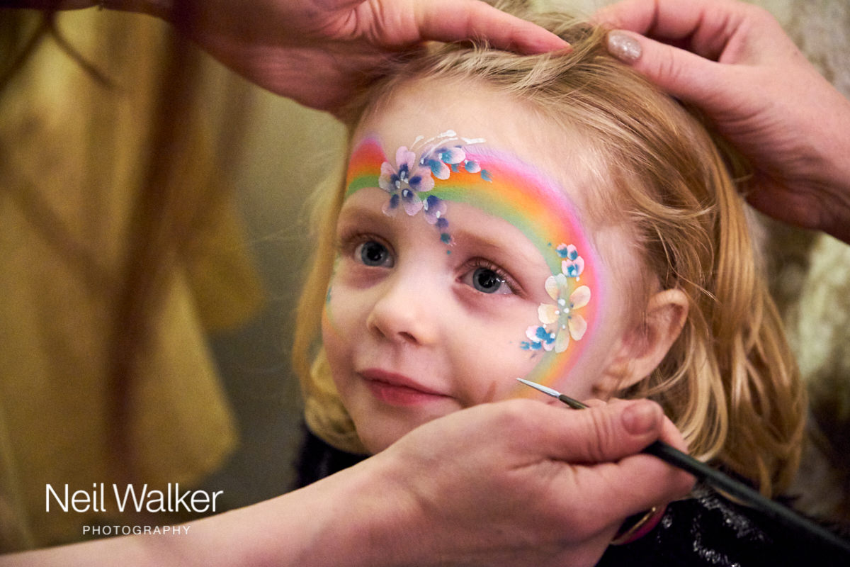 the bride and groom's daughter having her face painted