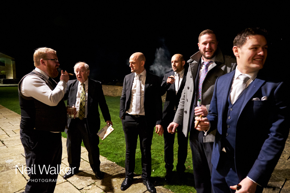 the groom and his groomsmen having a cigar outside the venue