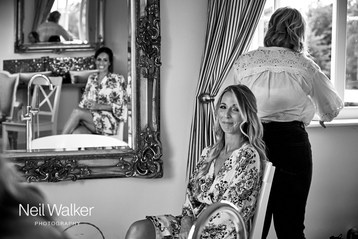 a bridesmaid smiling at the bride in a mirror
