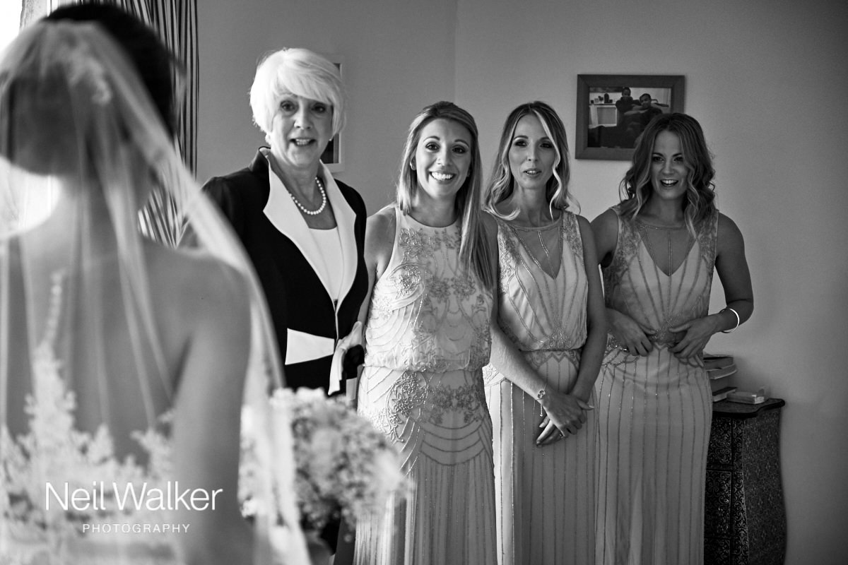 the bridesmaids smiling at the bride