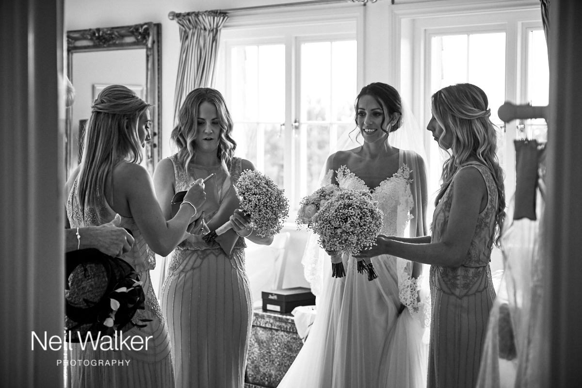 the bride and bridesmaids getting their bouquets ready