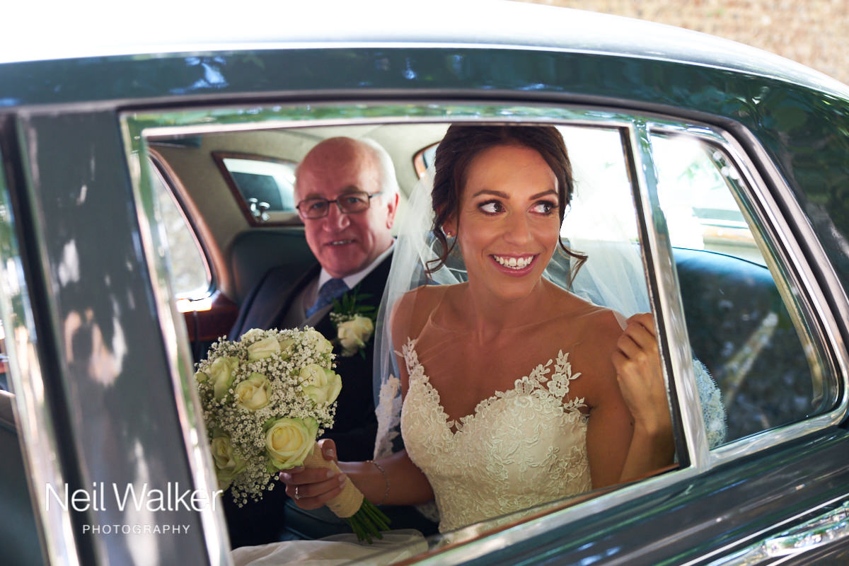 the bride arriving in the wedding car with her father