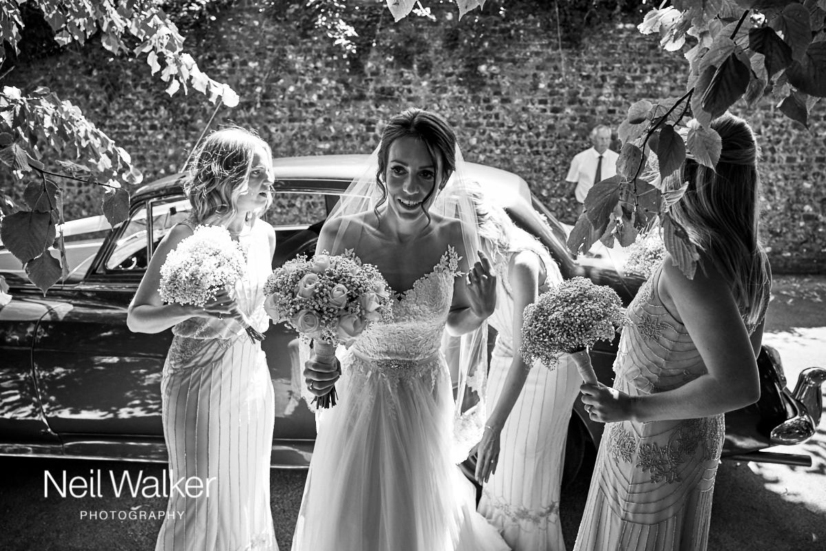 the bride with her bridesmaids after getting out of the wedding car