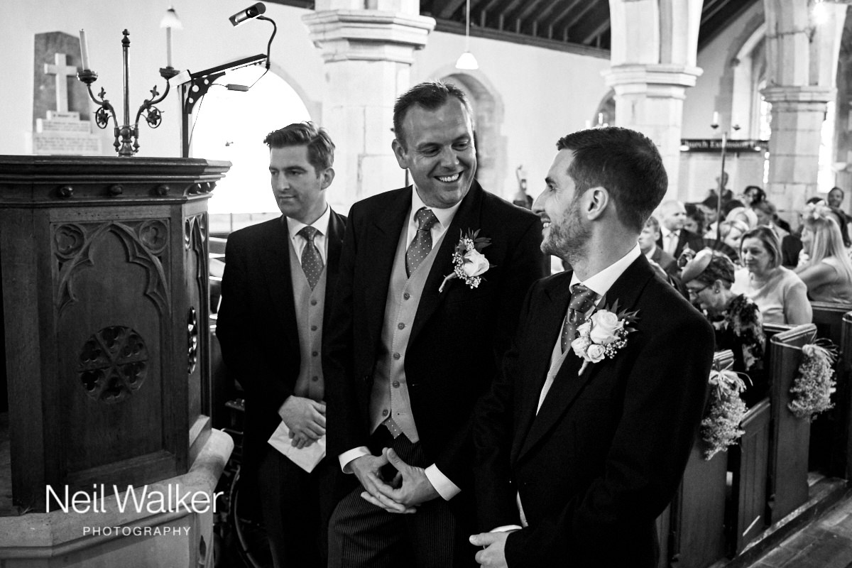 the best man laughing with the groom while they wait for the bride