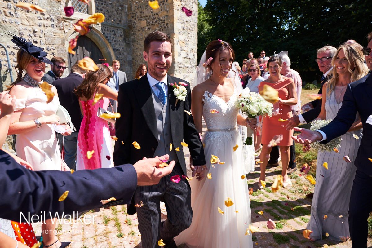 the bride and groom having confetti thrown on them
