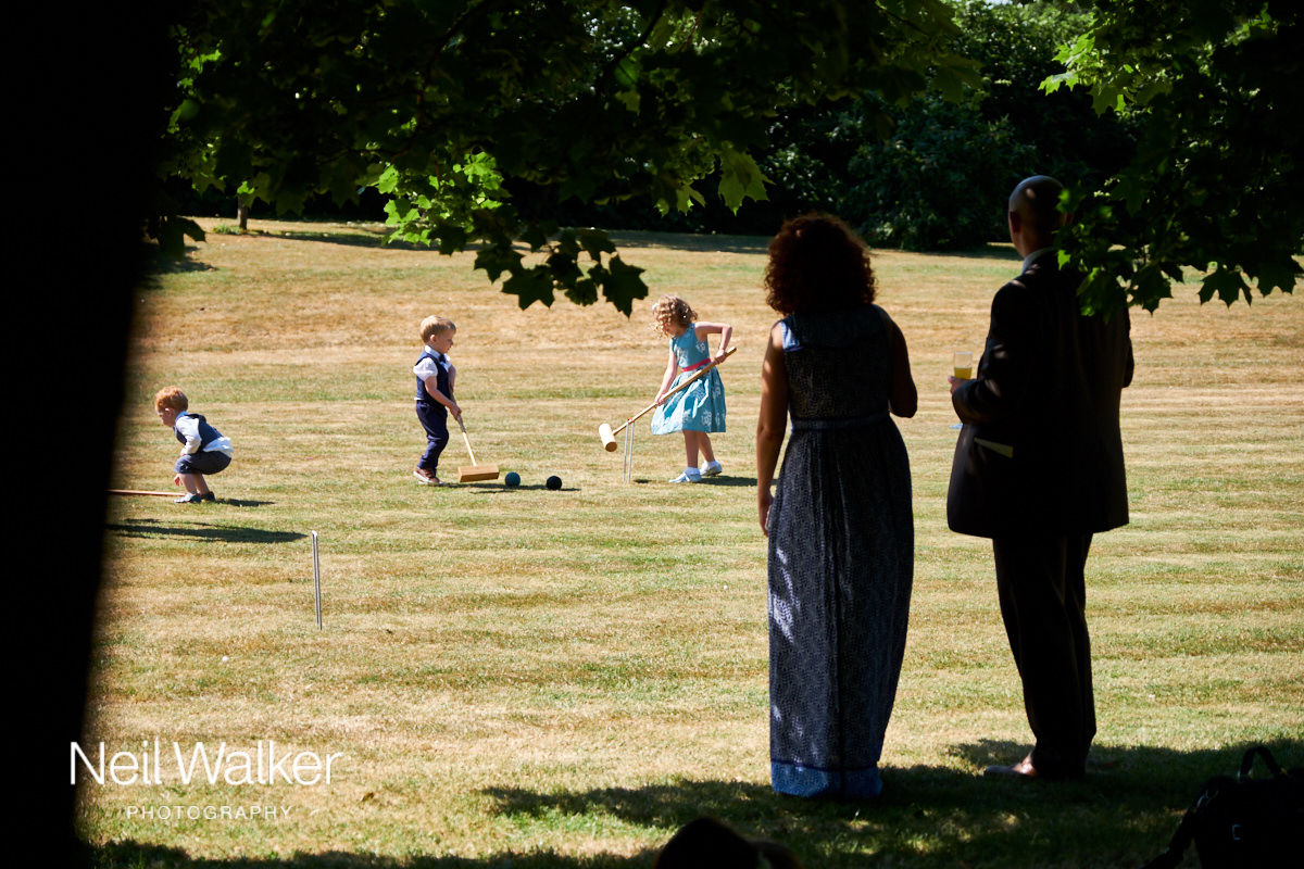 some children playing croquet on the lawn
