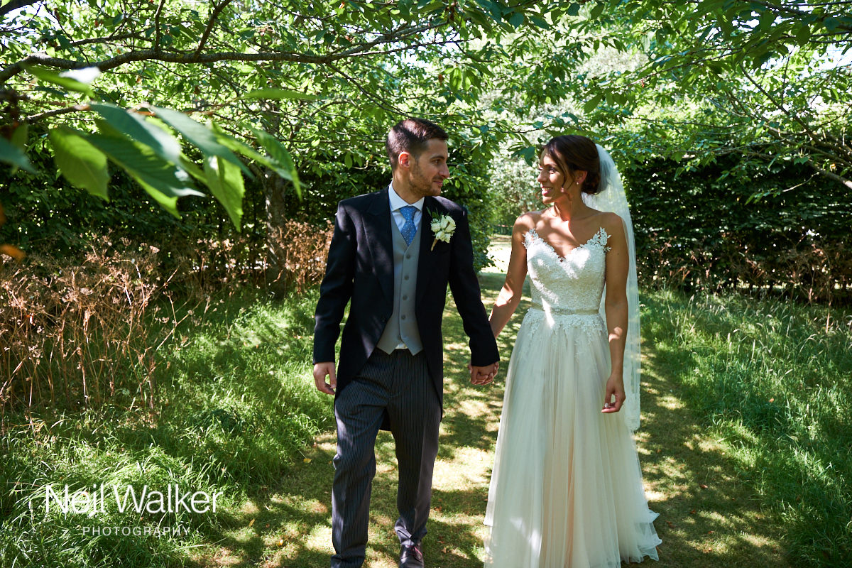 the bride and groom walking in the sunlight under the trees