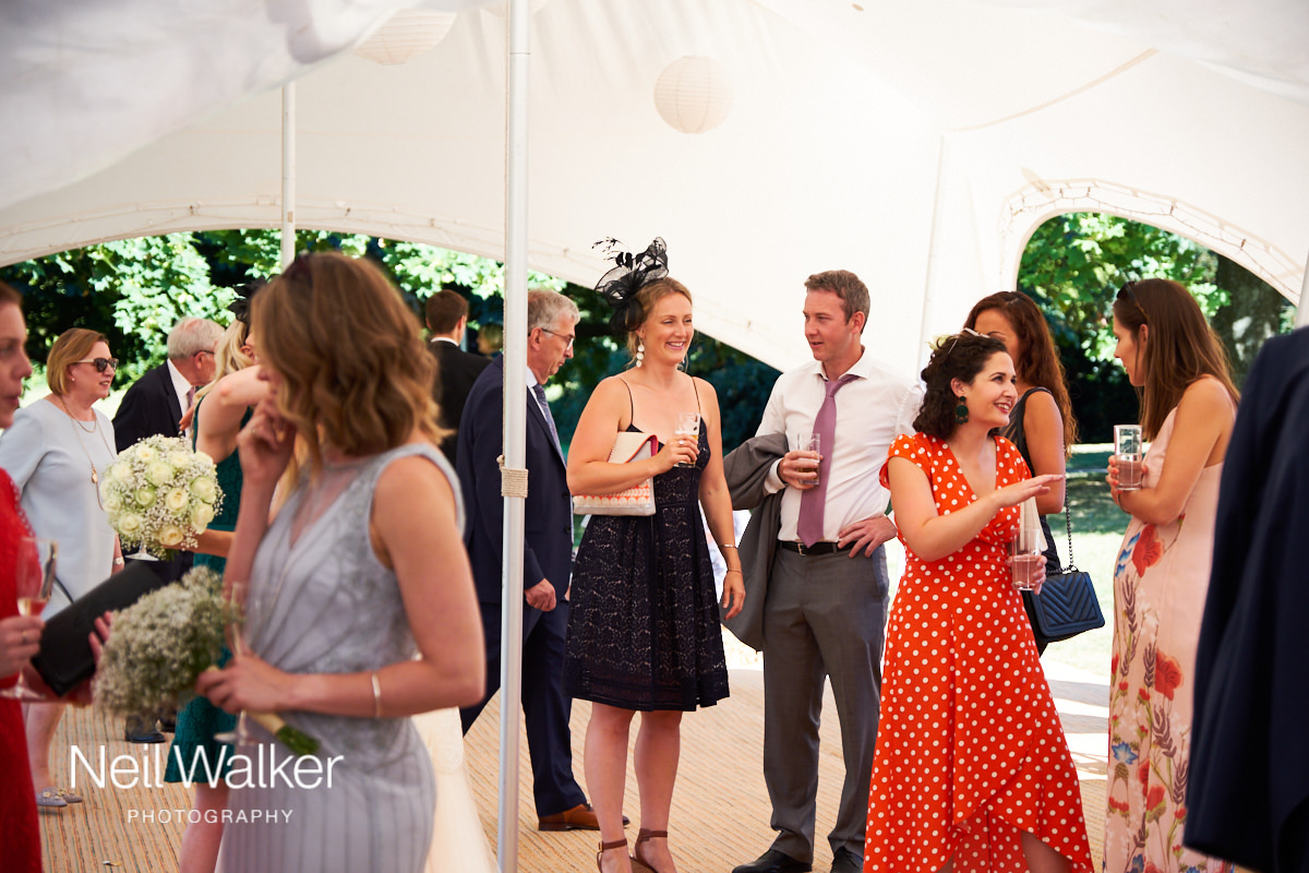 guests at a wedding talking in the marquee on a sunny summers day