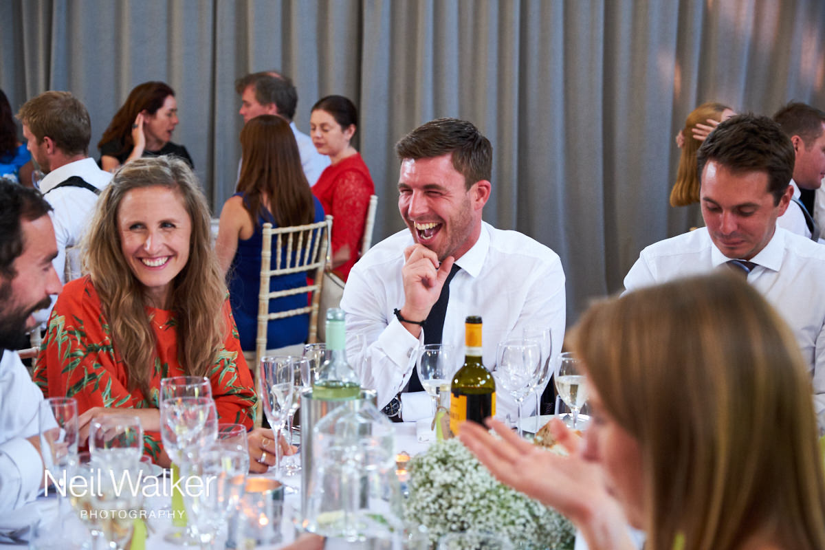 a guest laughing at a joke at the reception of a Sussex wedding
