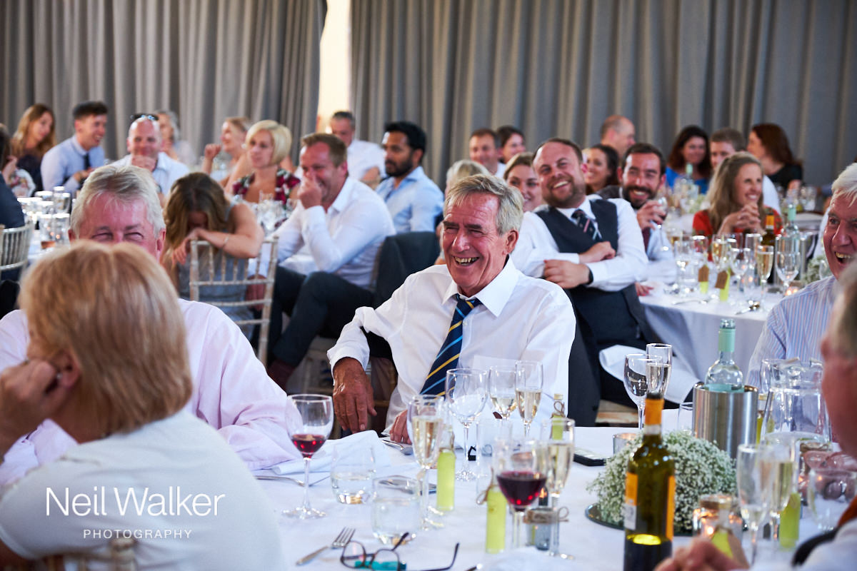a guest laughs at the speeches at a wedding