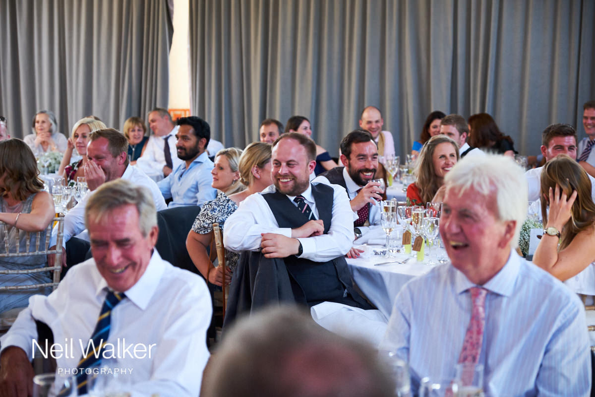a guest at a wedding laughing at the speeches