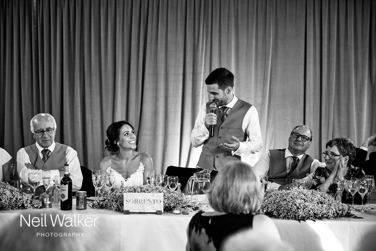 the bride and groom look at each other during his speech