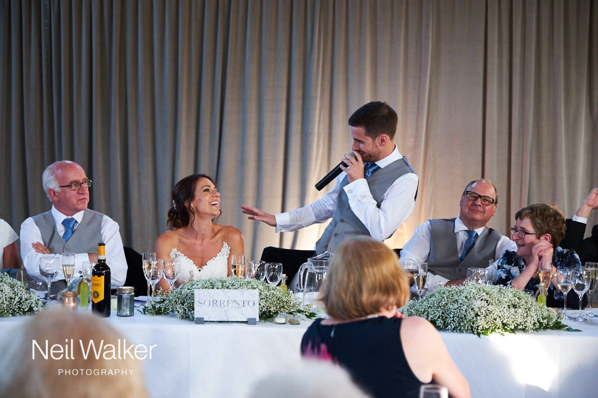 the bride laughs at the groom's speech