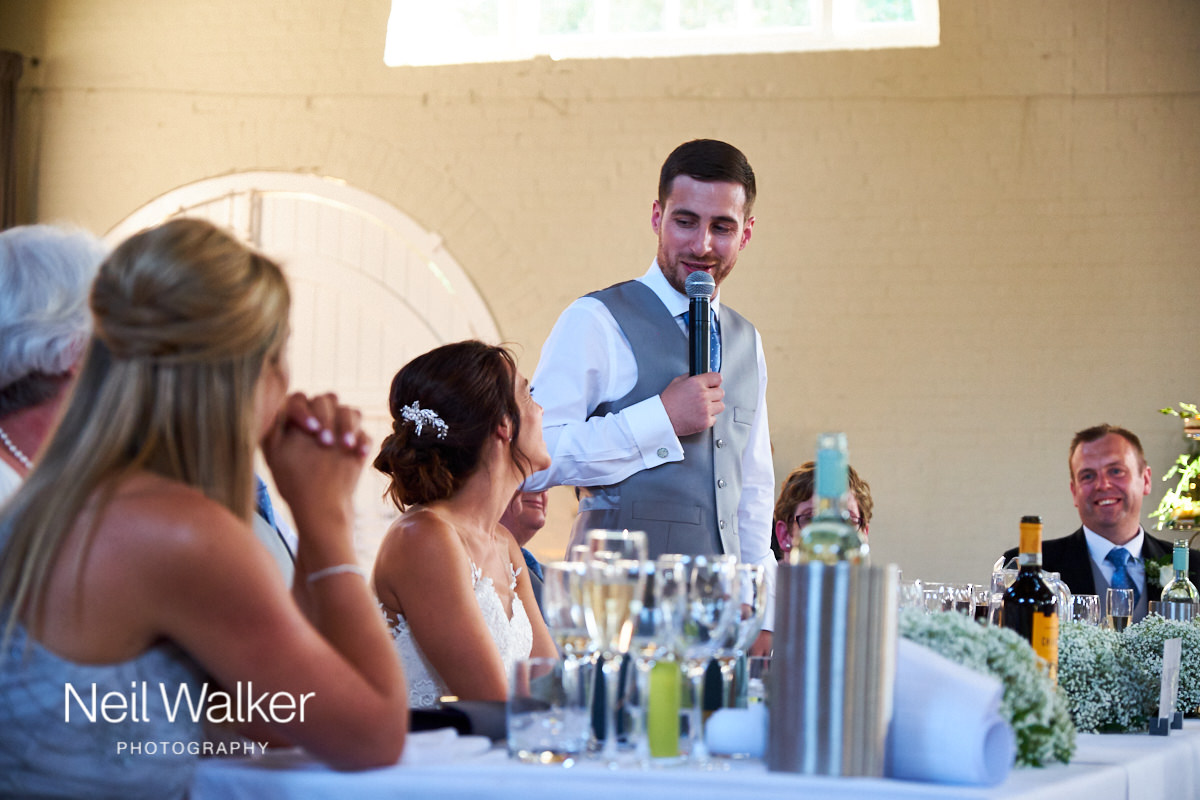 the groom looking at the bride during his speech