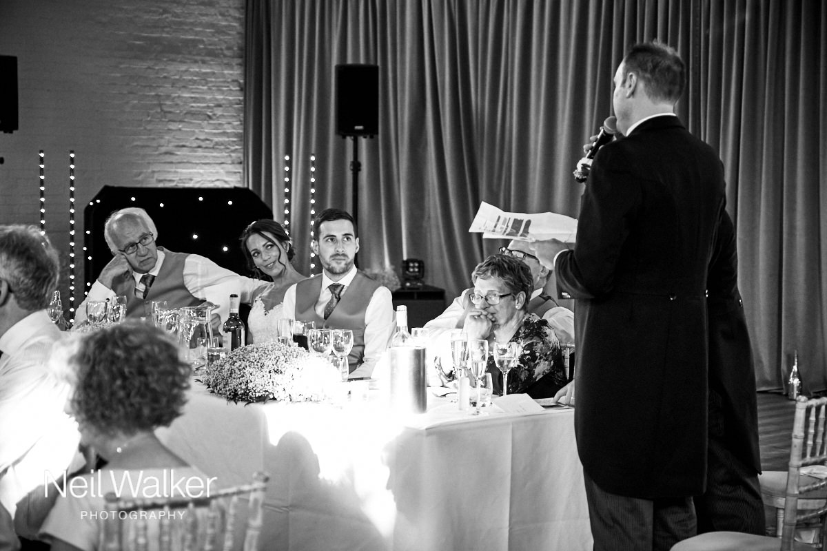 the groom looking at the best man during his speech