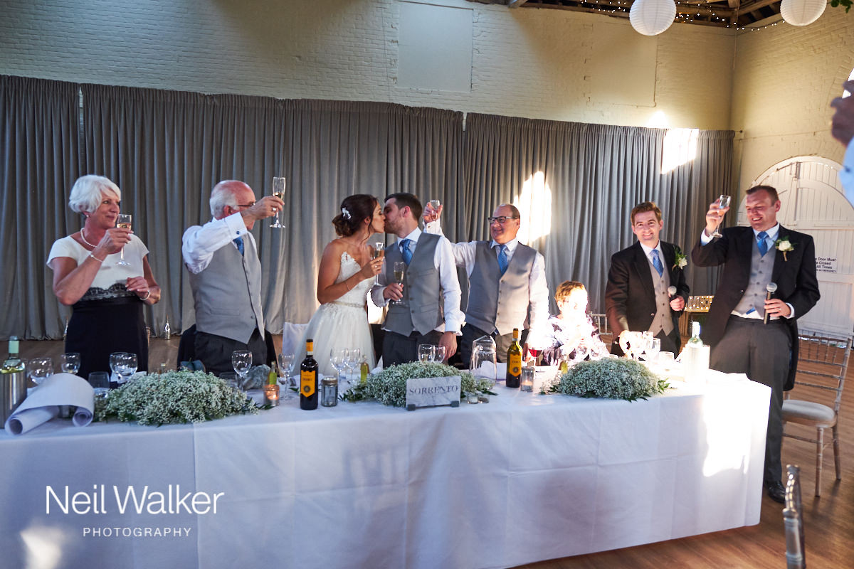 the bride and groom kiss while guests cheer
