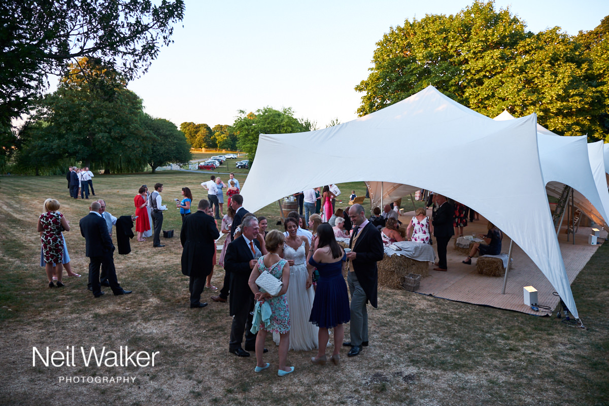the guests at a Sussex wedding enjoy the shade on a hot summers day