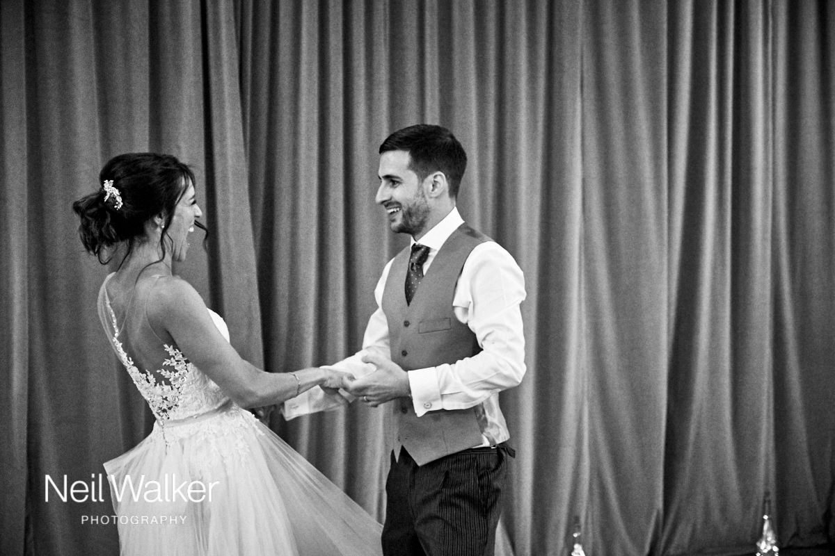 the bride and groom laugh together as they dance