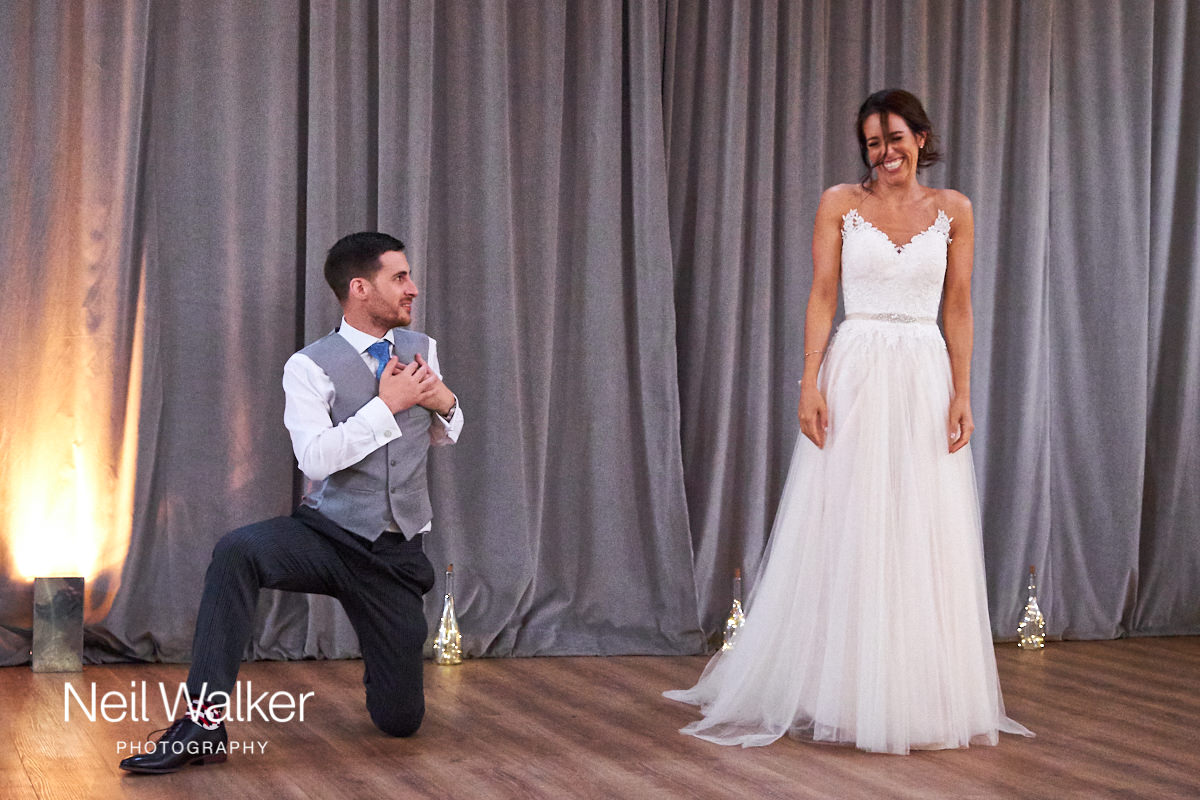 the groom goes down on one knee during the happy couple's first dance
